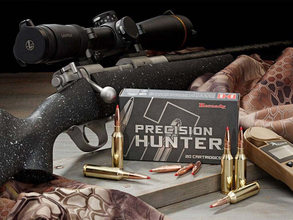 A box of Hornady rifle ammo next to a bolt-action rifle.