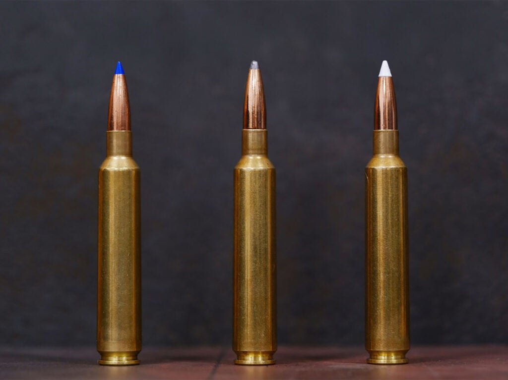 Three rifle cartridges standing up on a table.