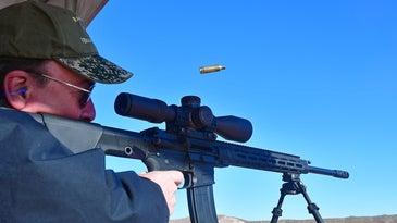 A hunter aiming a rifle at a shooting range.