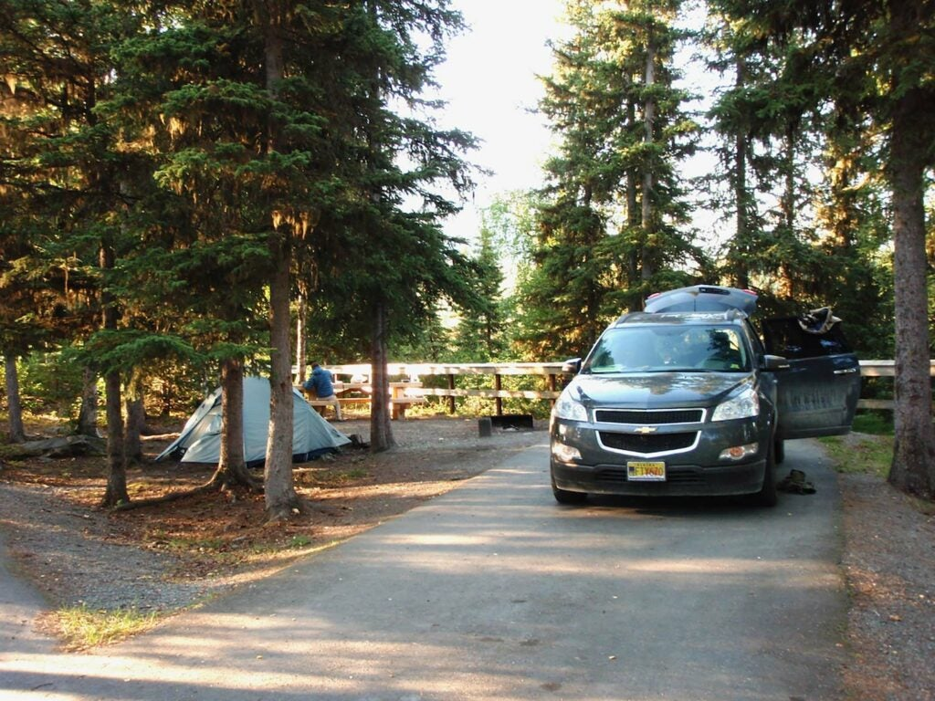 A small hunting campground with a Chevrolet vehicle parked nearby.