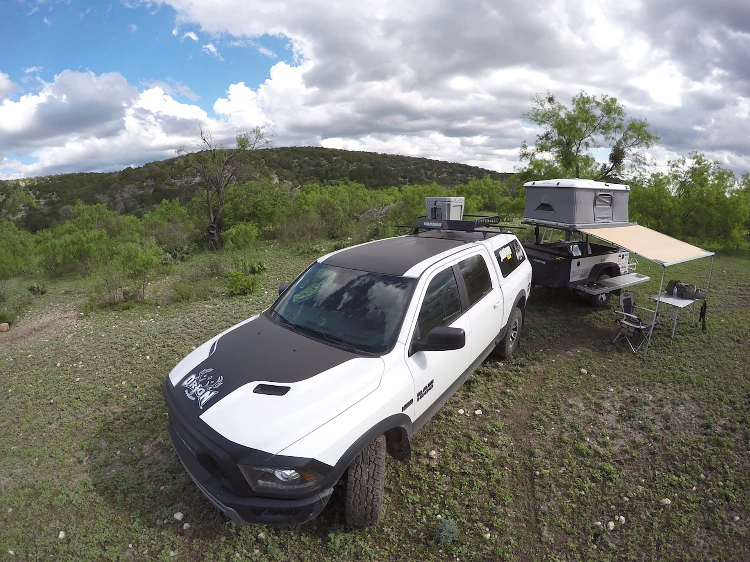 A white and black hunting vehicle next to a hunting camp.