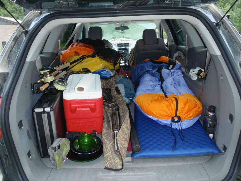 Piles of hunting and camping gear packed into the back of a hunting vehicle.