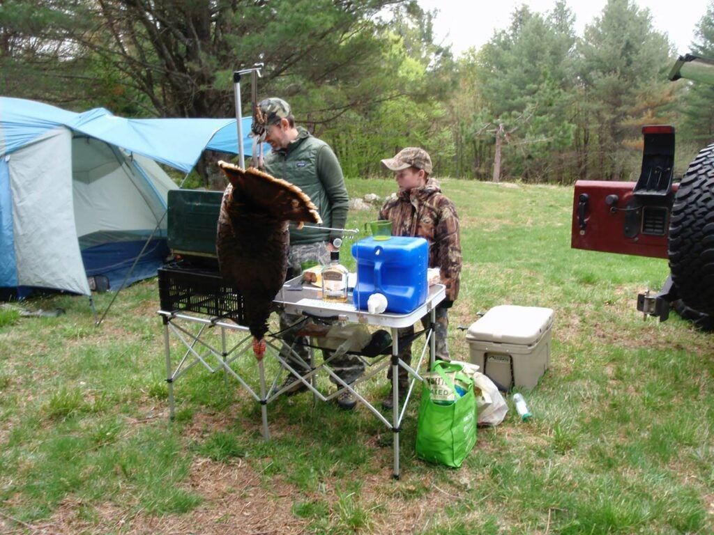 Two hunters cooking at a campground.