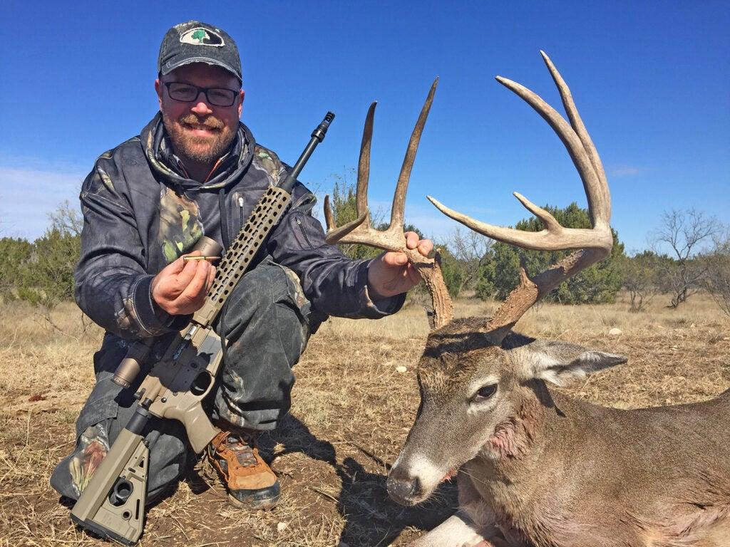 A hunter kneeling next to a large whitetail deer.