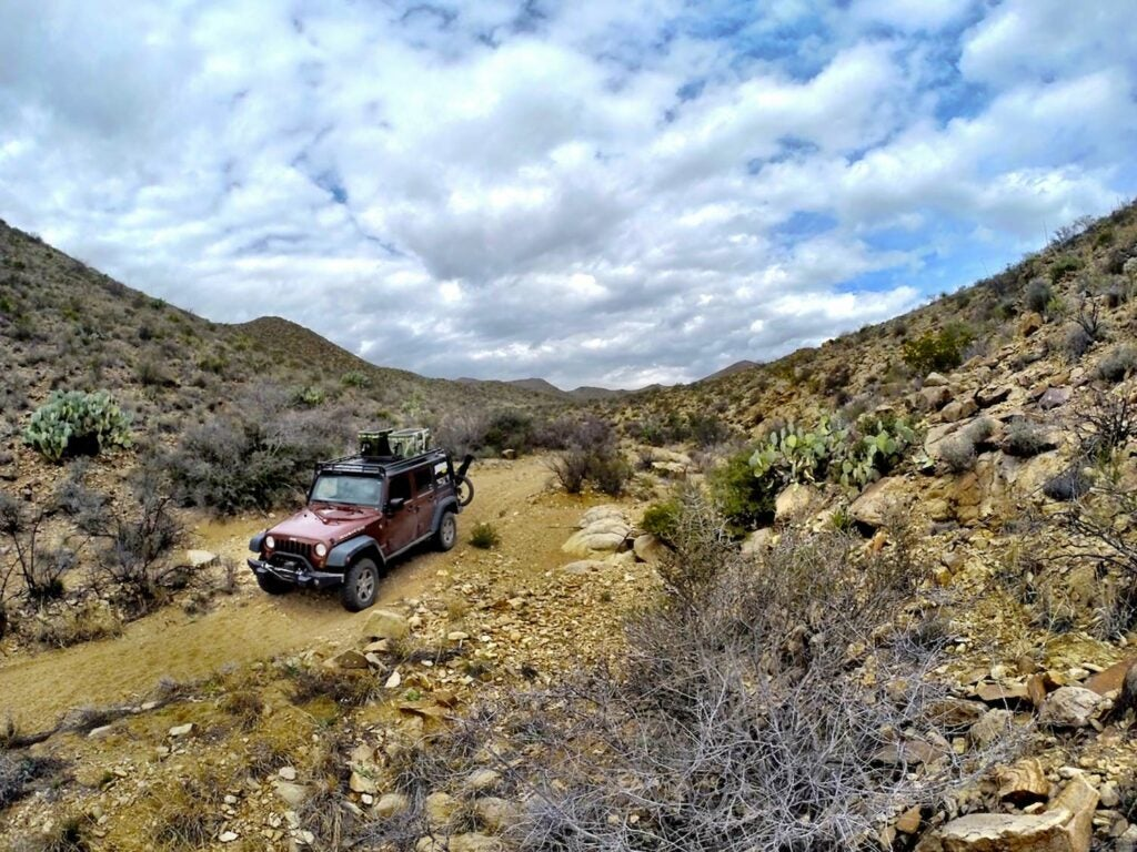 A Jeep Wrangler Rubicon in red drives through an overland hunting trail.