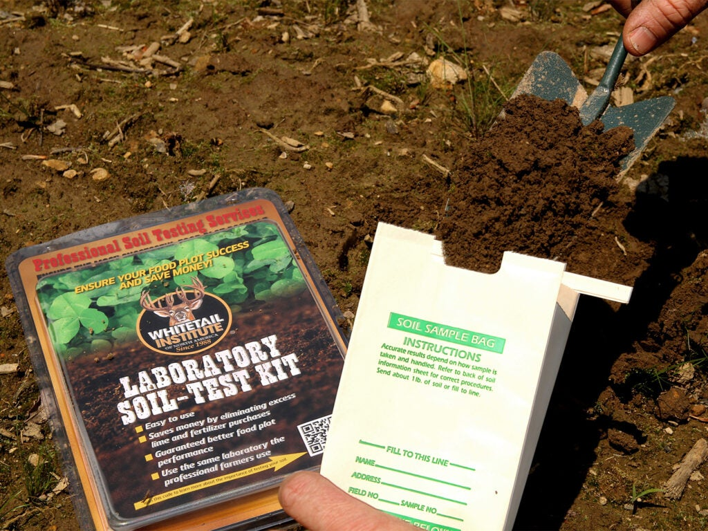 A hand scoops a soil sample into a box for soil testing.