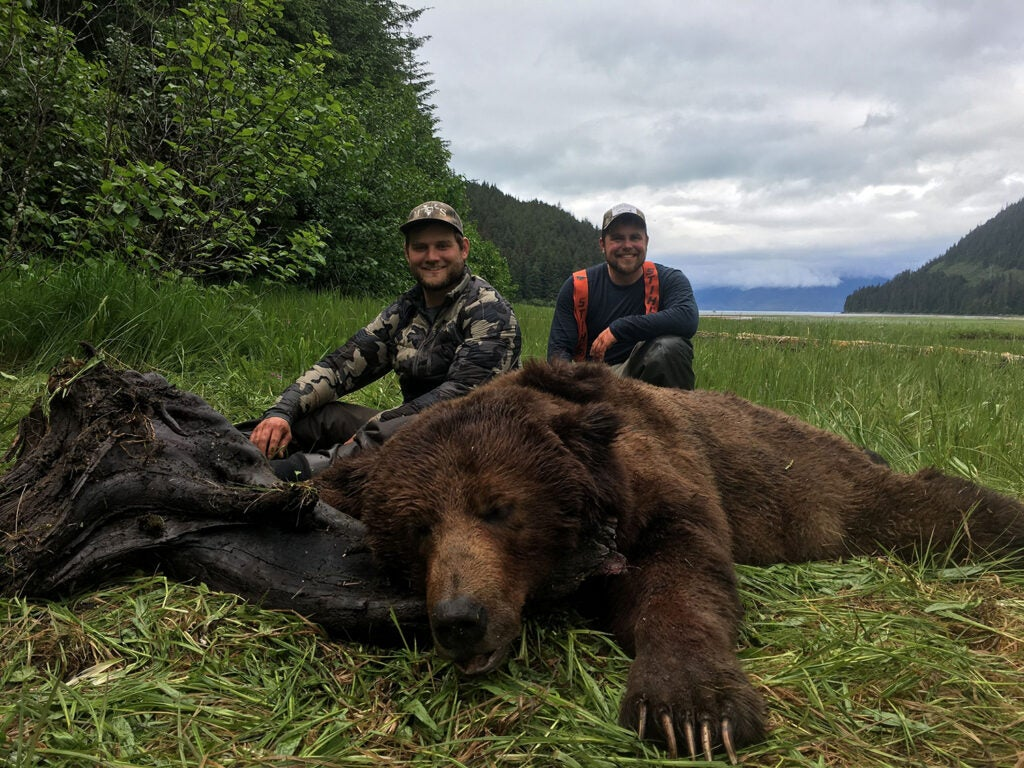A hunter kneeling beside a large brown bear in the Tongass National Forest.