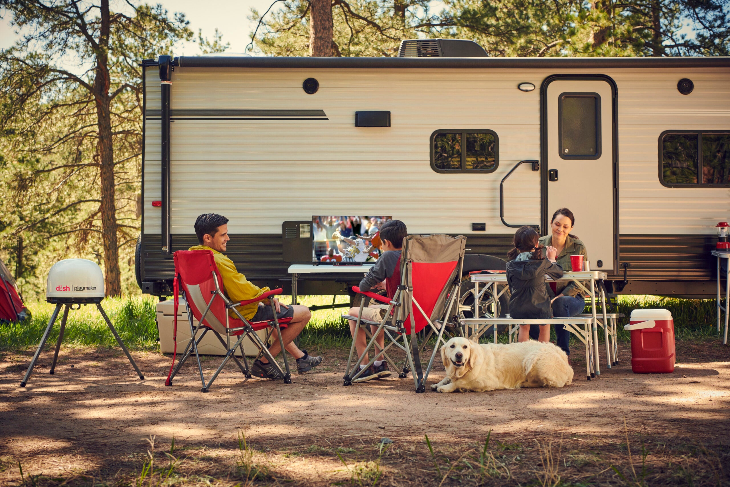 A campsite with people and dogs and a DISH Outdoors and television.