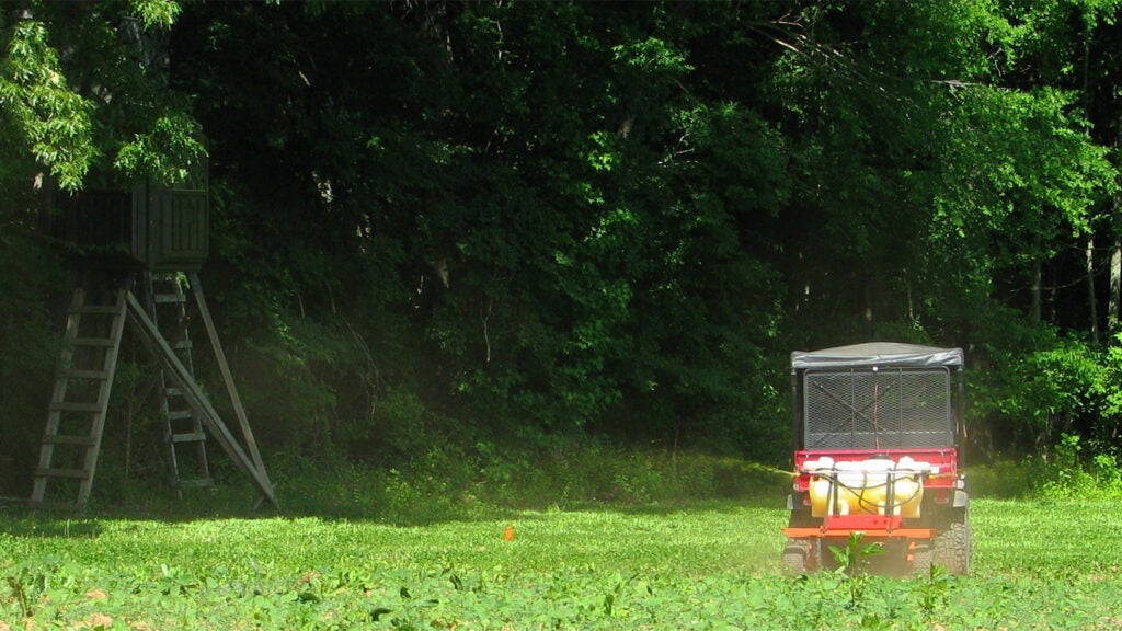 A small UTV spreads fertilizer and weed spray in a food plot field.