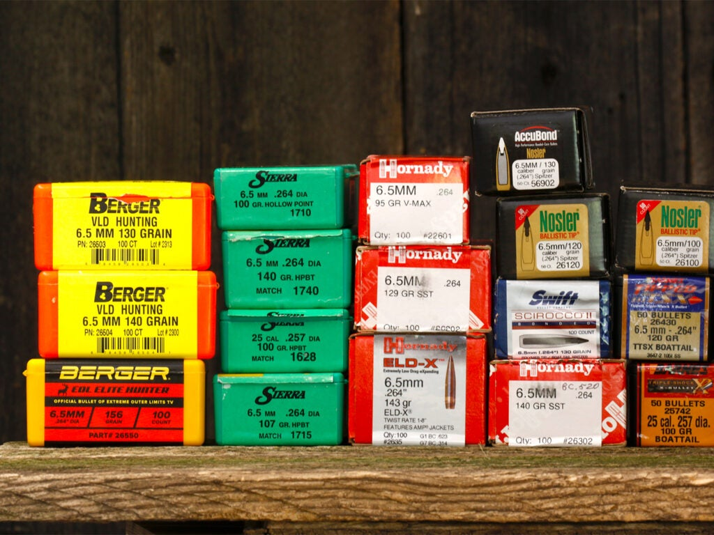 Several boxes of rifle ammo on a wooden table.