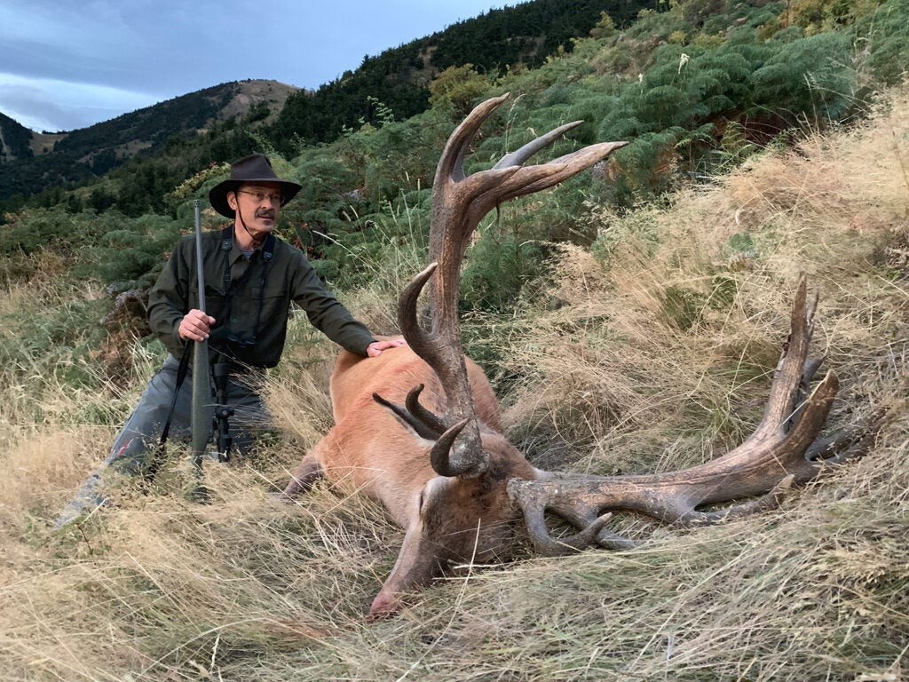 A hunter kneeling next to a large big red stag.