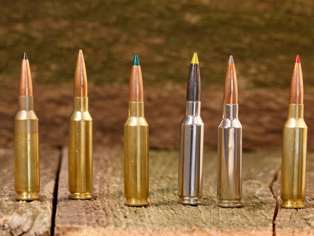 A lineup of 6.5 Creedmoor rifle cartridges on a wooden table.