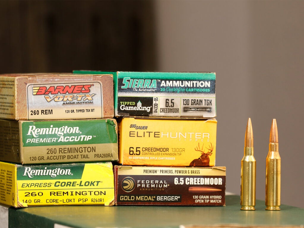 Six boxes of rifle cartridges and bullets on a table.