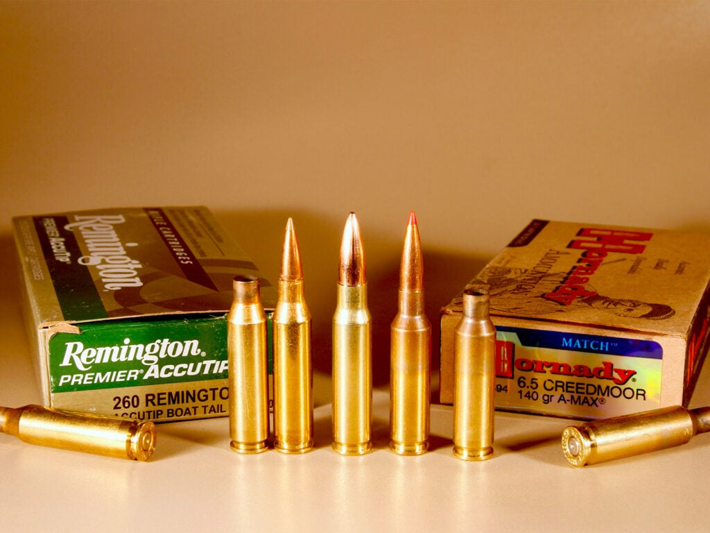 Two boxes of ammo and a lineup of rifle cartridges on a table.