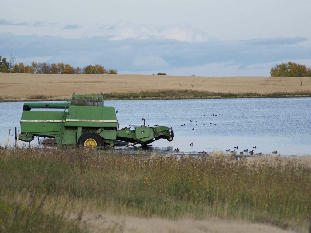 A green tractor stuck in the mud on a lake.