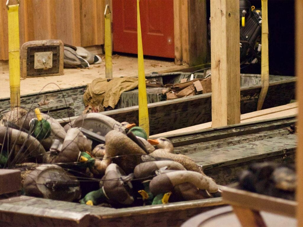 Piles of duck decoys and gear in a storage room.