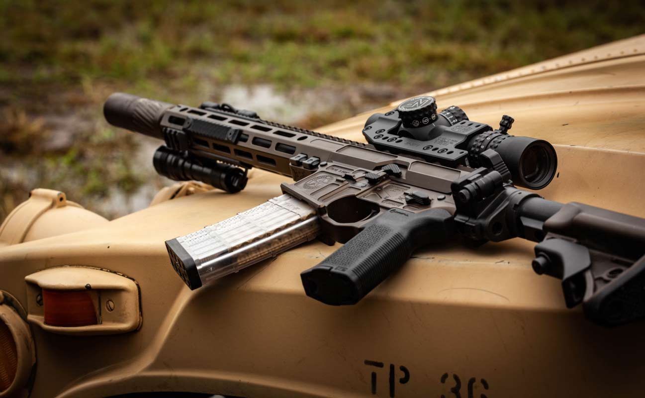 A Lone-Star TX15 AR-15 Rifle on the hood of a tan utility vehicle.