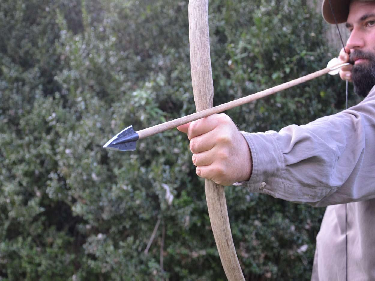 A man with a beard draws back on a hand-made bow and arrow set.
