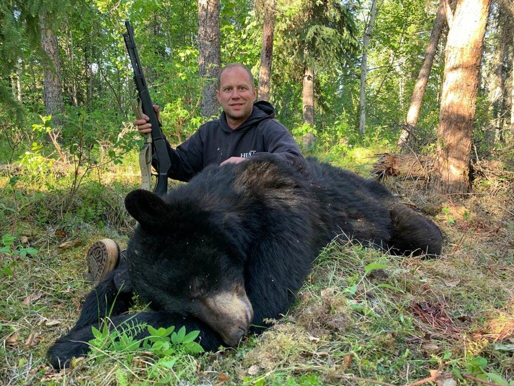 A hunter holds a rifle while kneeling behind an Alaskan Black Bear.