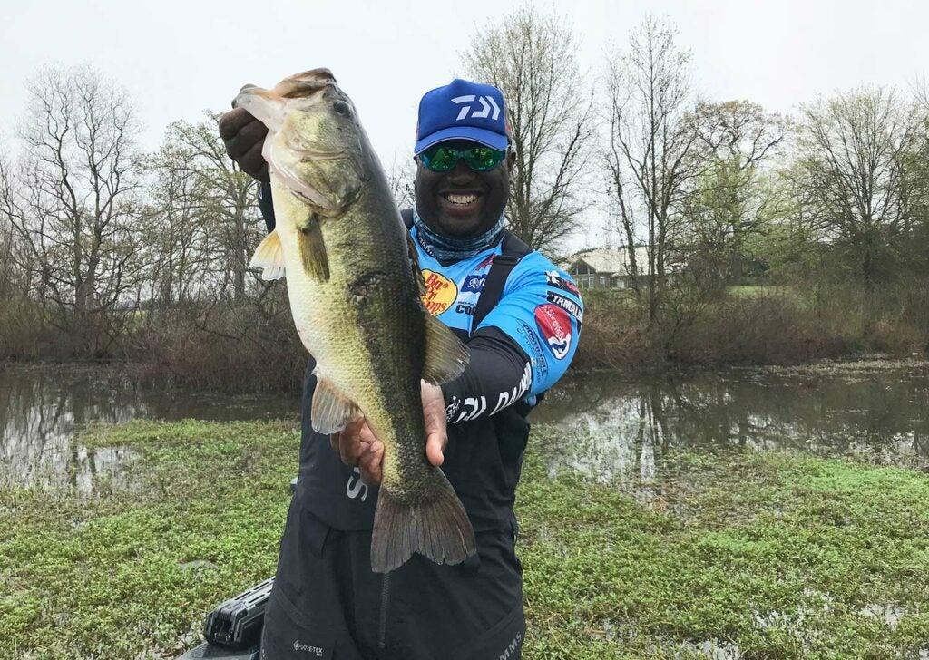 A fisherman holding up a largemouth bass.