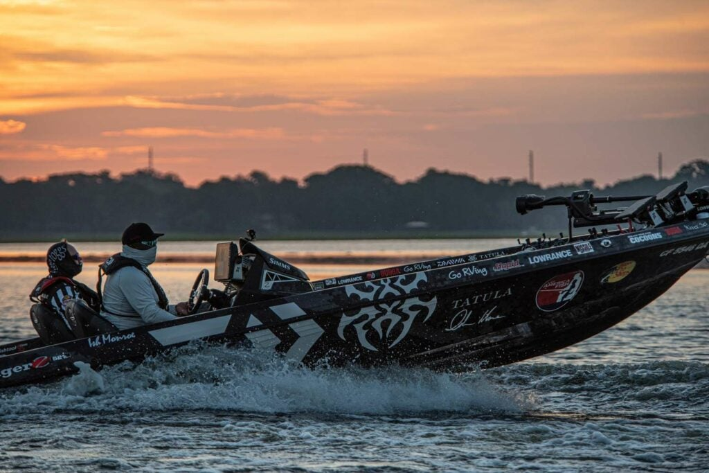 Two anglers on a bass fishing boat at sunset.