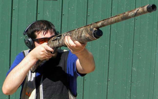 A man in shooting gear aiming a Baikal shotgun.