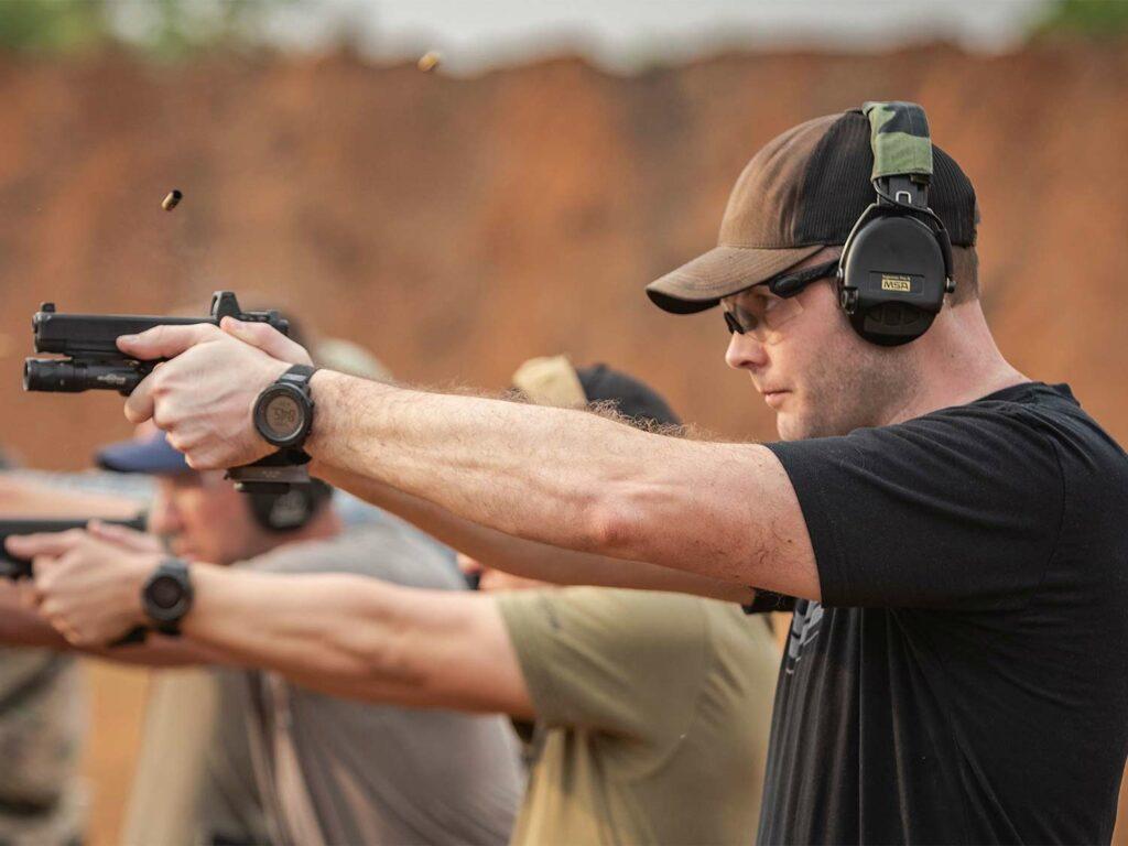 A man aiming a handgun at a shooting range.