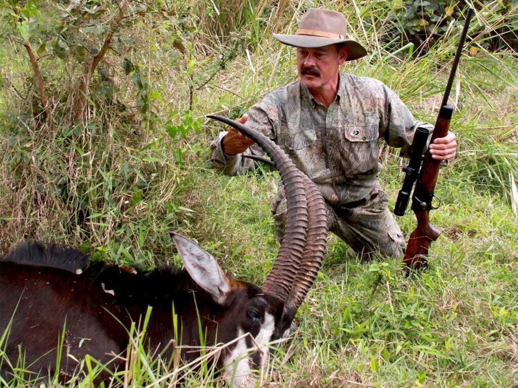 A hunter kneels beside a dead antelope.