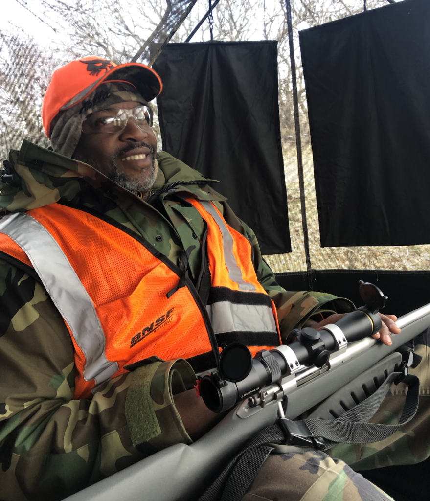 A hunter sitting inside a screened-in blind with camo, blaze orange, and a rifle across his lap.