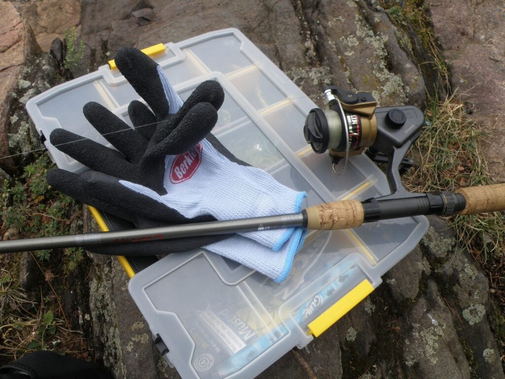 A fishing glove, rod, and reel resting on a tackle box.