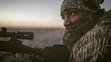 A black man in hunters camo holds a rifle.