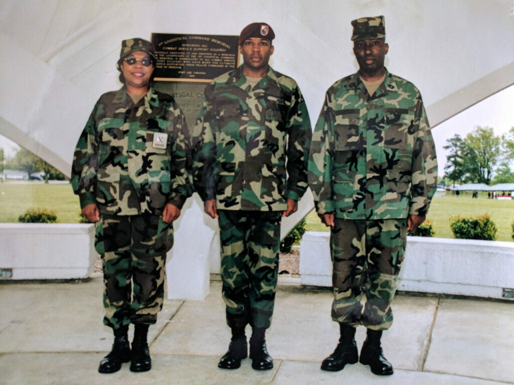 A mother, father, and adult son in army fatigues, standing at attention in Fort Lee, Virginia.