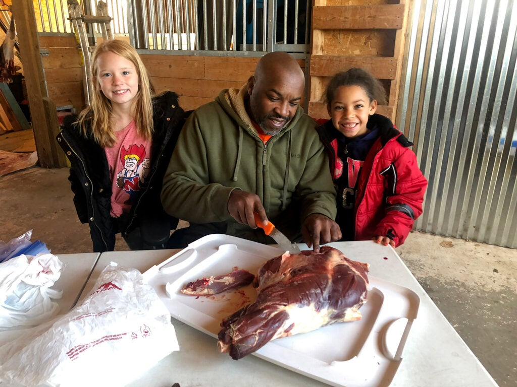 A black man carves and butchers deer meat while two kids stand beside him.