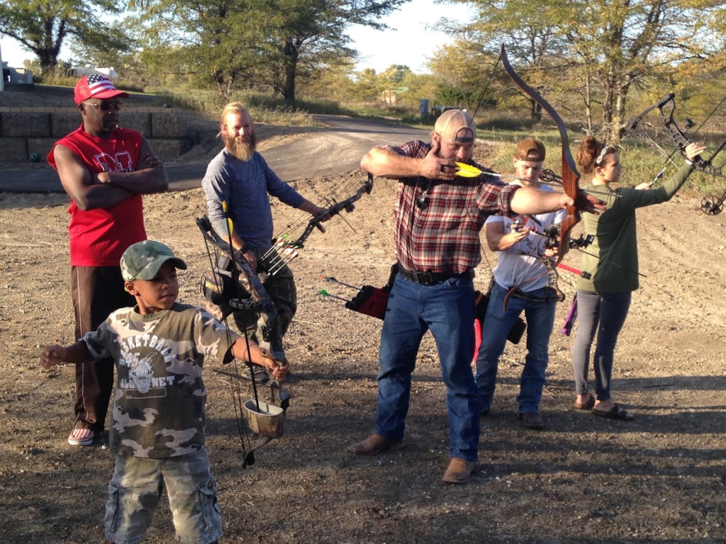Group of bearded men and a kid shooting traditional bows for target practice