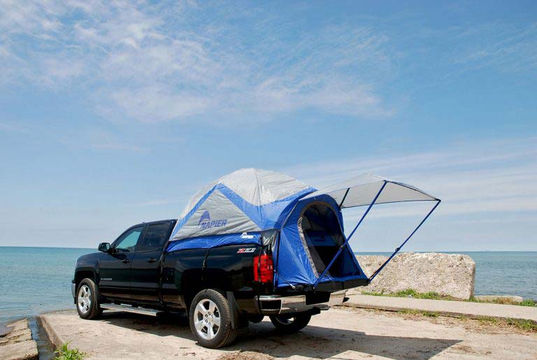 A truck outfitted with a tent in the truck bed.