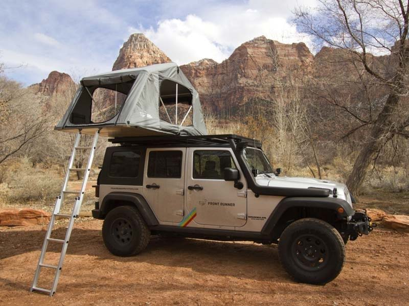 A camping tent on the hood of a white jeep.