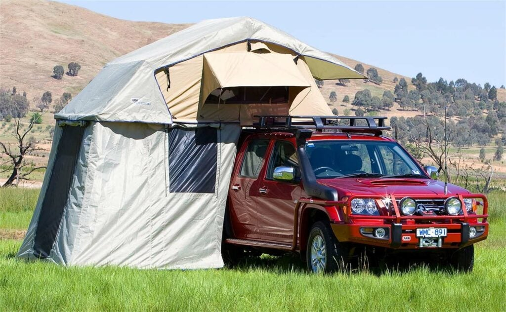 A red outdoor vehicle with a camping tent attached to it.