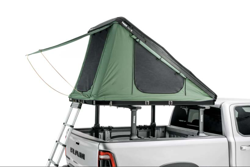 A box wedge camping tent in the bed of a white RAM truck.