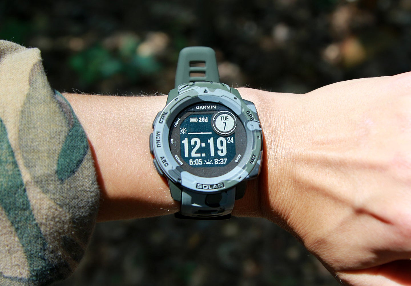 A large camo smart watch face on a wrist, in the sunshine.