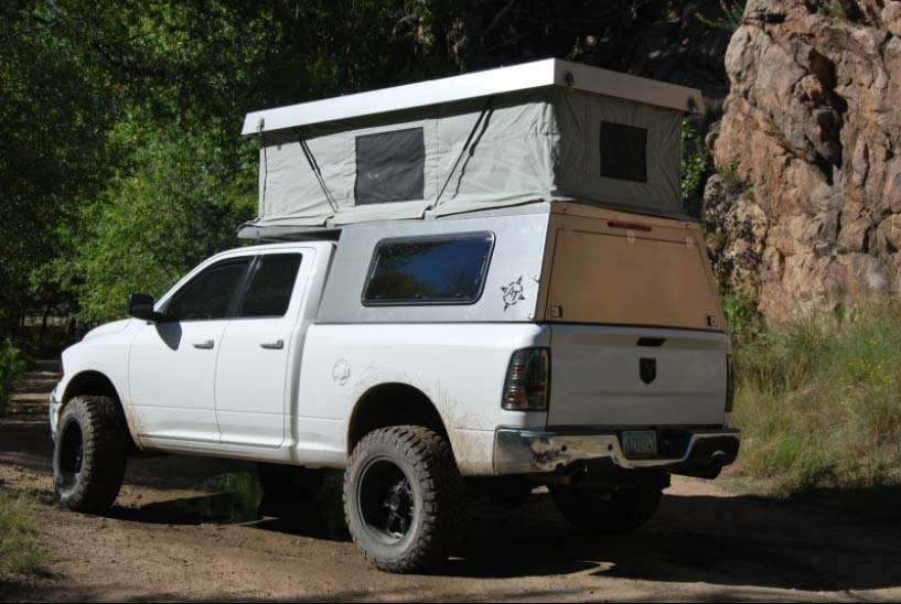 A camping tent and hard top on the bed of a white truck.