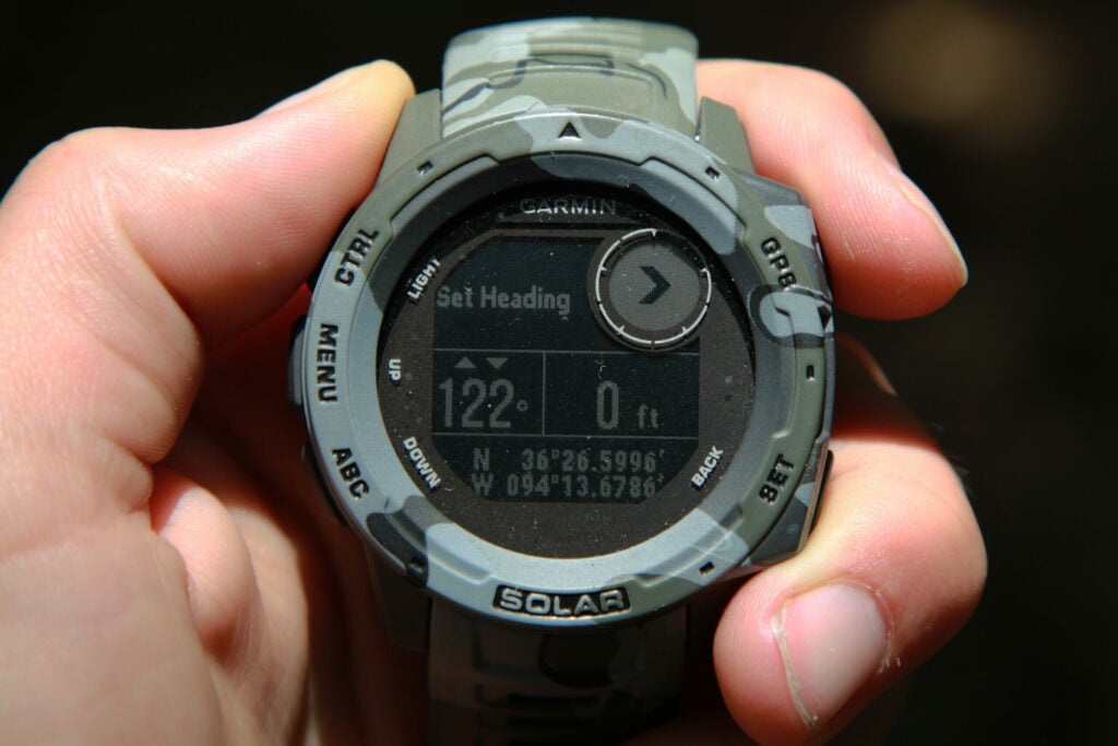 A hand-held camo Garmin GPS smart watch with a display reading