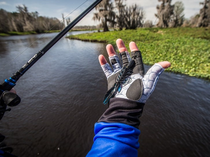 A hand holding a punch bait lure for bass fishing.