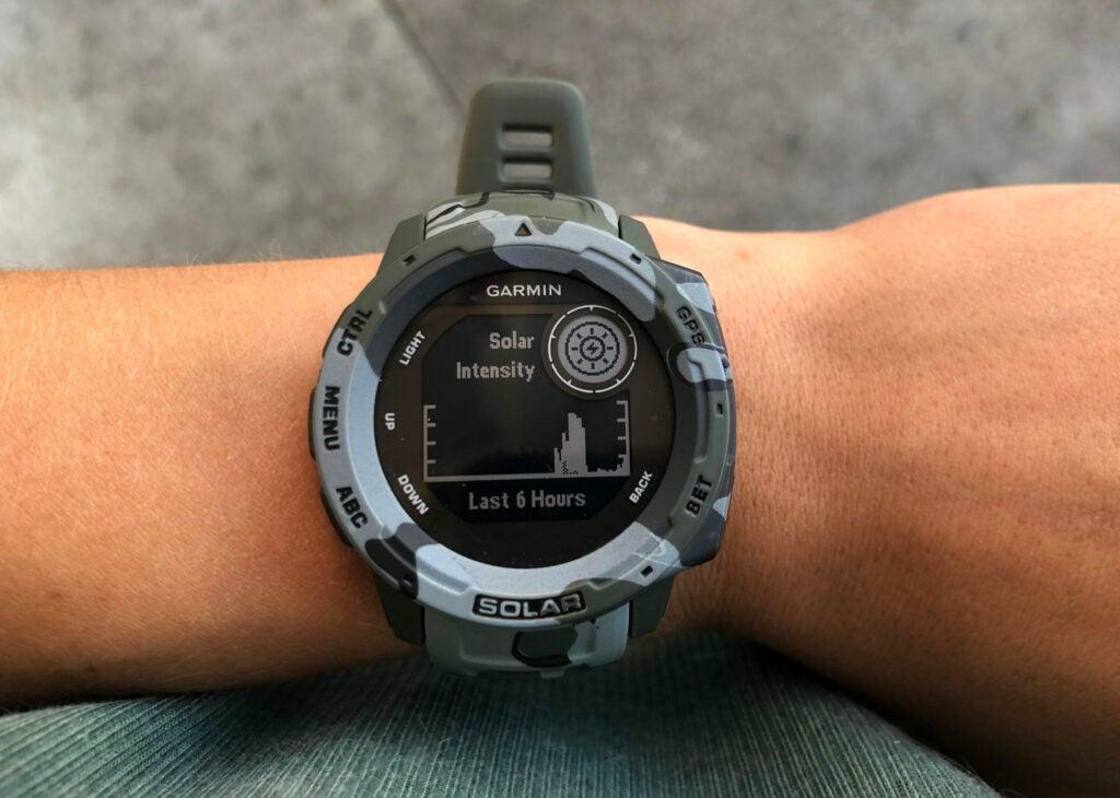 A camo Garmin smart watch displaying a graph on sun exposure.
