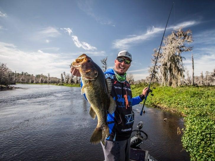 A bass fishing angler holds up a largemouth bass.
