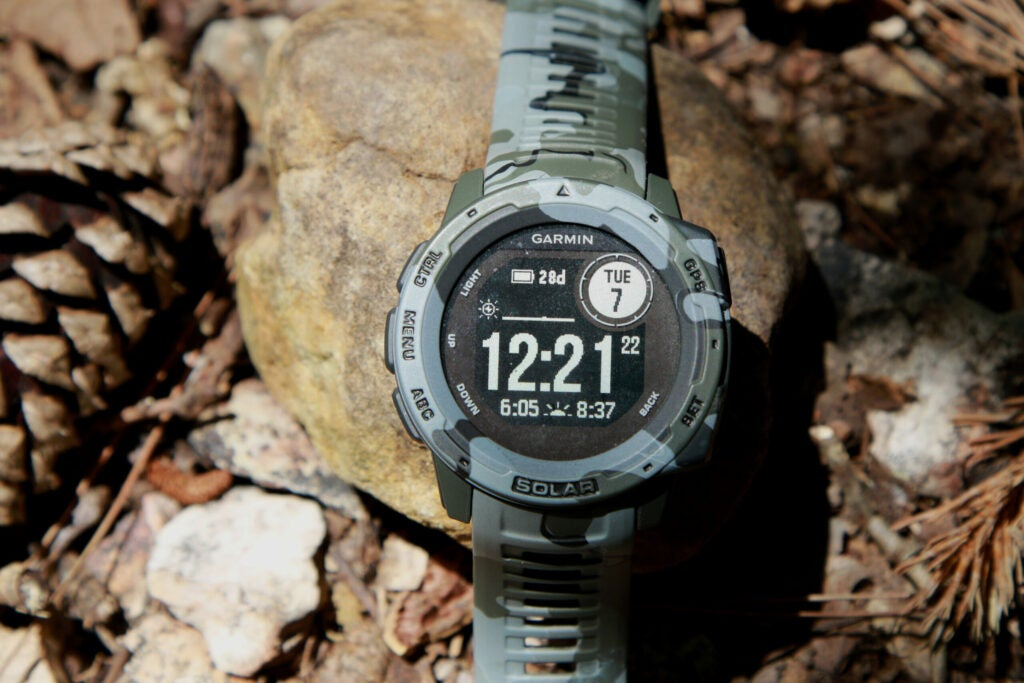 A camo watch displaying the time 12:21 and a battery life of 28 days on a rocky background.