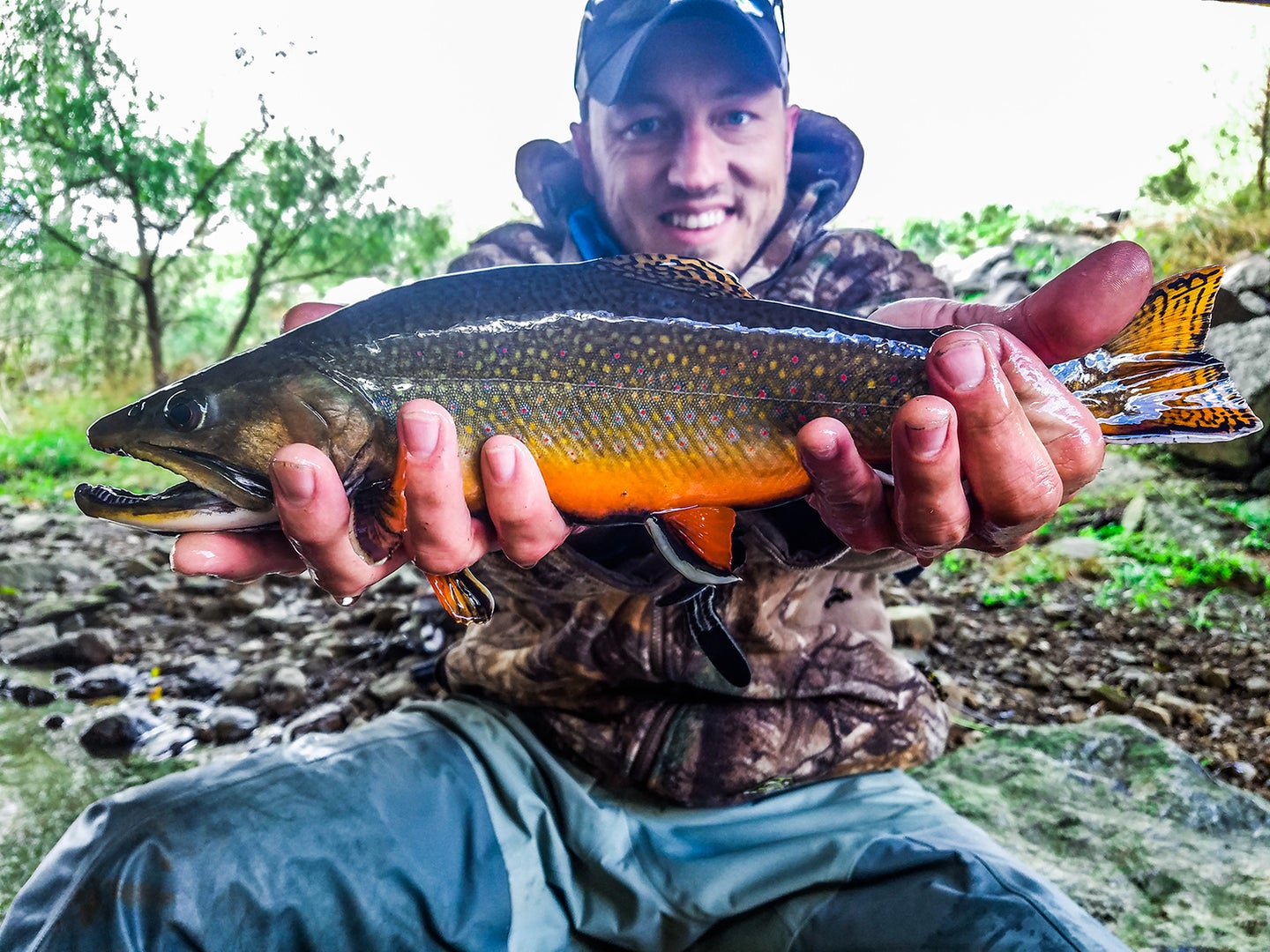 A white male in camo and blue jeans holds up a large brook trout in two hands.