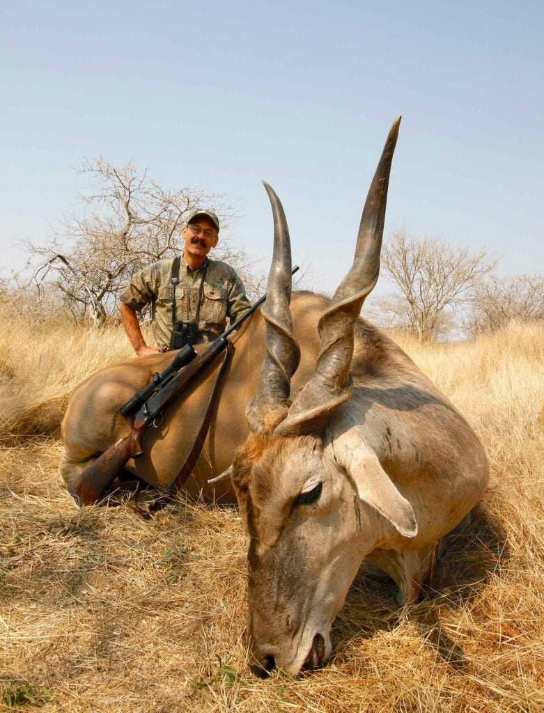Hunter standing beside a recently killed 1,800-pound Namibian eland