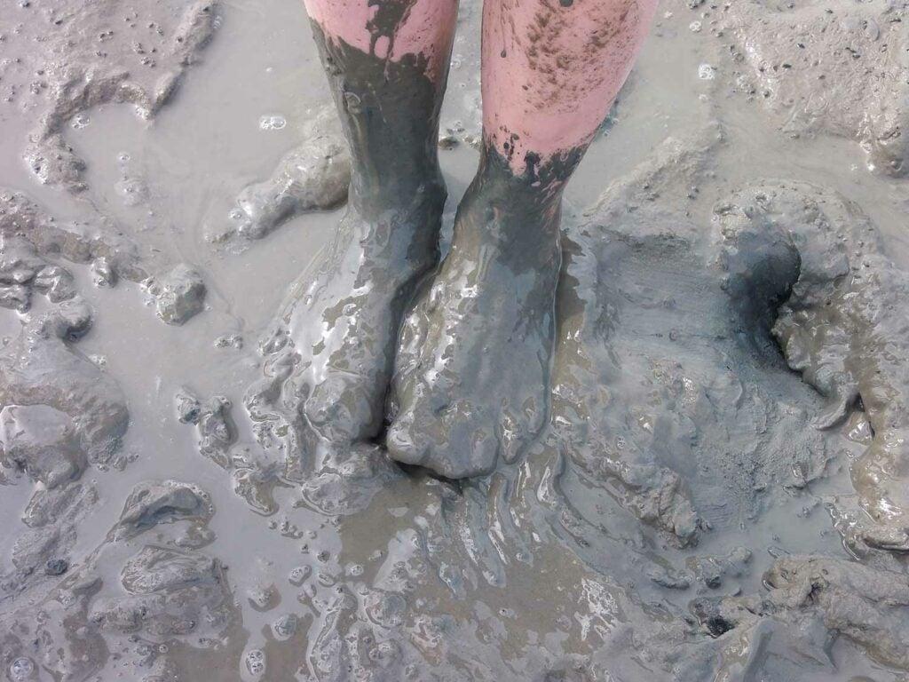 A pair of feet ankle deep in very wet mud.