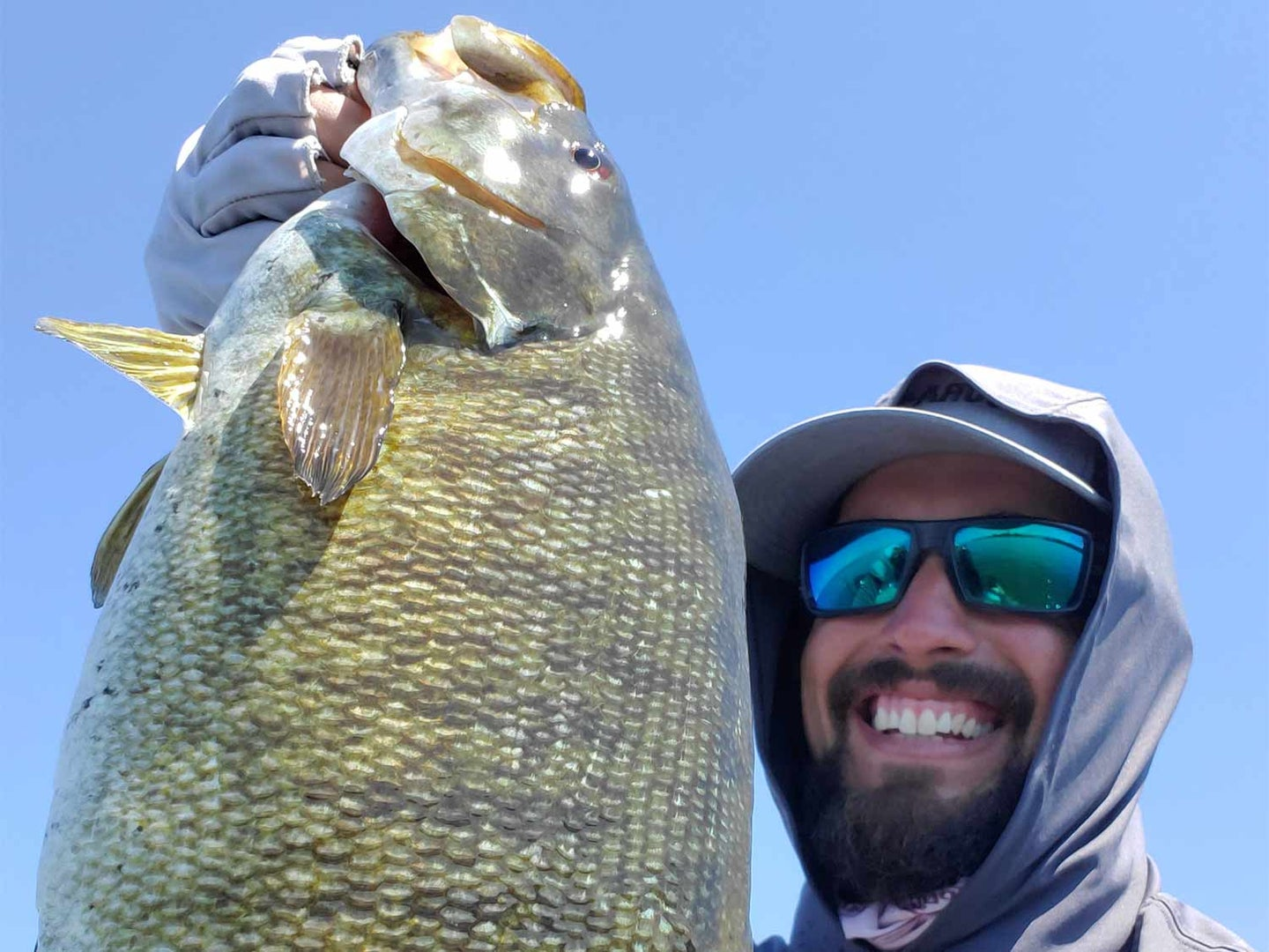 A angler in a cap and hoodie holds up a large smallmouth bass.