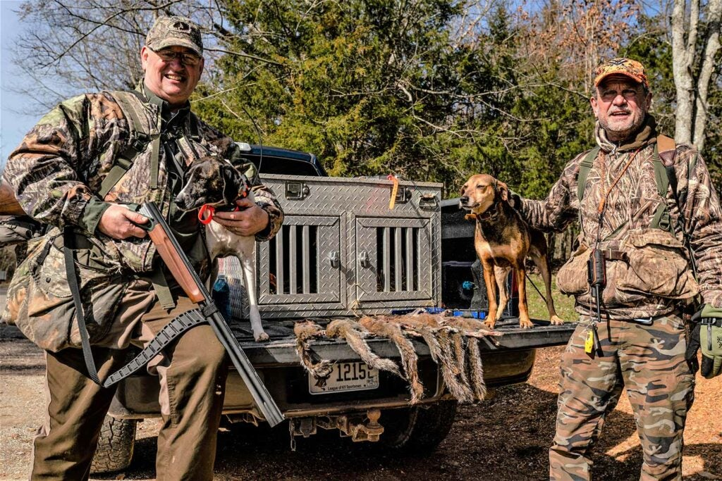 Two hunters standing next to a truck with a hunting dog on the tailgate.